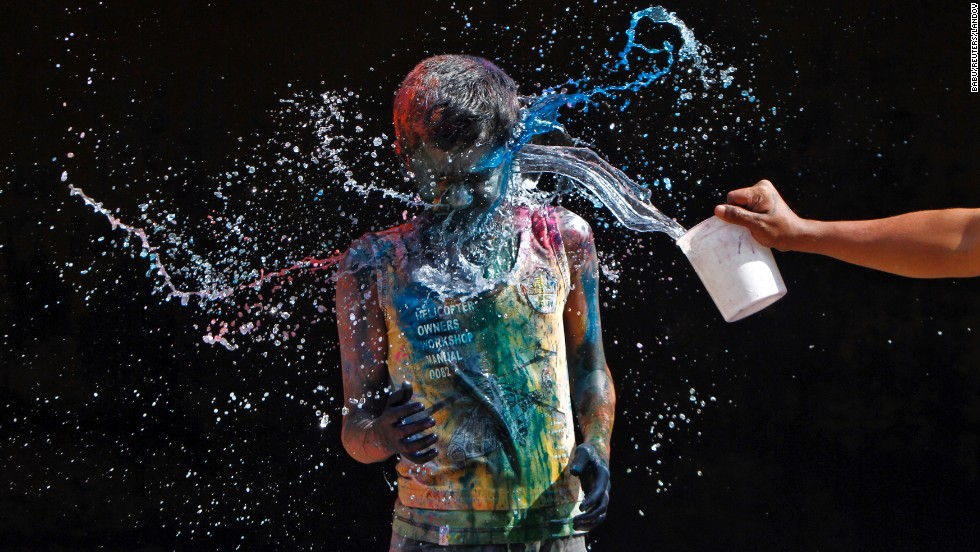 A boy splashes water on another boy smeared with colors in Chennai on March 27.