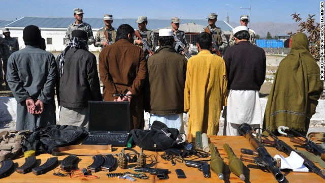 Taliban fighters stand handcuffed near seized weapons at a police headquarters in Jalalabad on March 2, 2013.