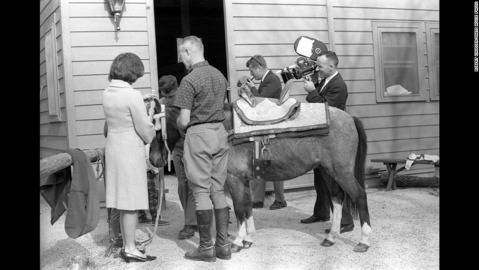 Jackie Kennedy assists two unidentified men with the harnessing and saddling the pony. The president smokes a pipe while a cameraman films the moment.