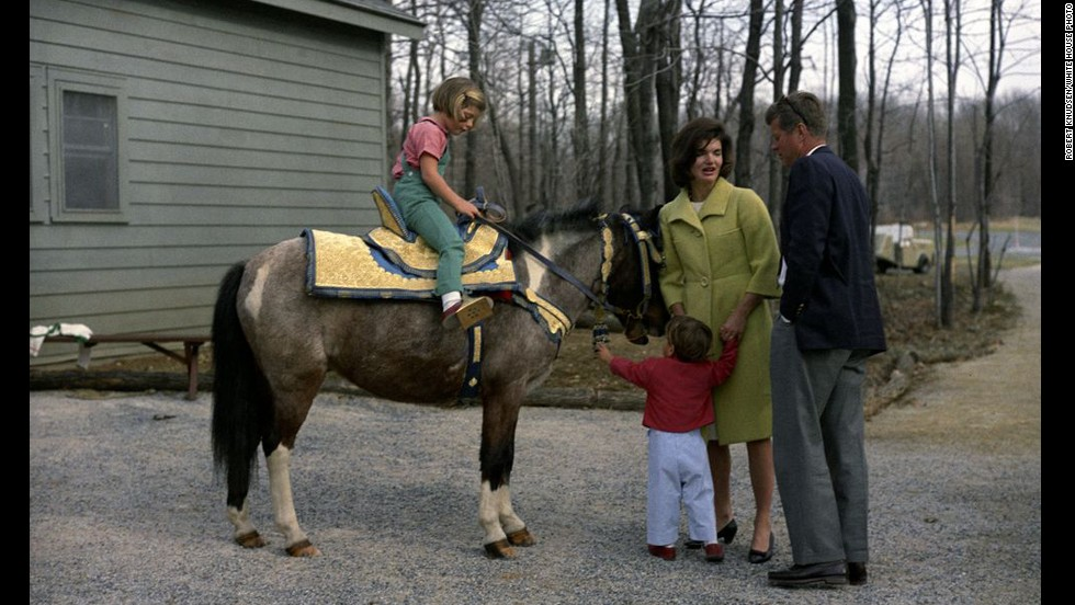 A recently released series of rare photos show President John F. Kennedy and his family enjoying a weekend at Camp David, 50 years ago this month. Here, the president and first lady Jacqueline Kennedy stand with John Jr., with daughter Caroline on horseback.