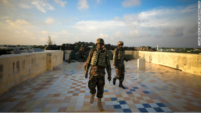 Soldiers walk across a defensive machine gun position on a hotel rooftop in the Yaaqshiid District of Mogadishu.