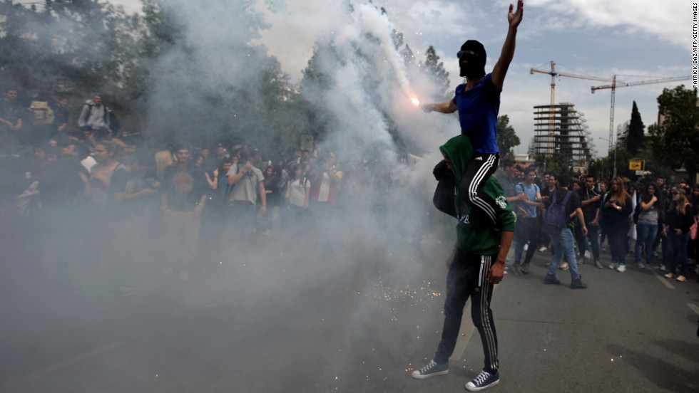 Cypriot college students light a flare outside the presidential palace during a protest on March 26.