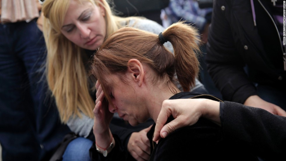 Employees of the Bank of Cyprus comfort one of their colleagues during a demonstration outside the main office of the bank in Nicosia on Tuesday, March 26.