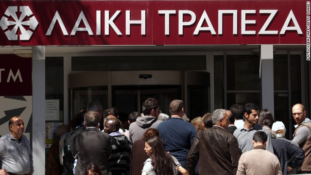 People queue up outside a Laiki bank branch in the Cypriot capital, Nicosia, on March 28, 2013, as they wait for the bank to open after an unprecedented 12-day lockdown. Queues of dozens of people formed before the doors swung open at 12:00pm (1000 GMT) for the first time since March 16, and there were tensions as a few branches opened late, with customers banging on the doors. AFP PHOTO / PATRICK BAZ        (Photo credit should read PATRICK BAZ/AFP/Getty Images)