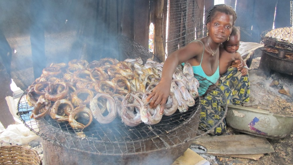 """""""The smoke bothers us but we have no other profession,"""" says fish merchant Emilienne. She sweats in the heat with her baby in-arm as she explains that hers is a typical role for women in Makoko. After the men bring back their catch of the day, their wives, mothers or sisters take the responsibility for preparing and selling the fish."""