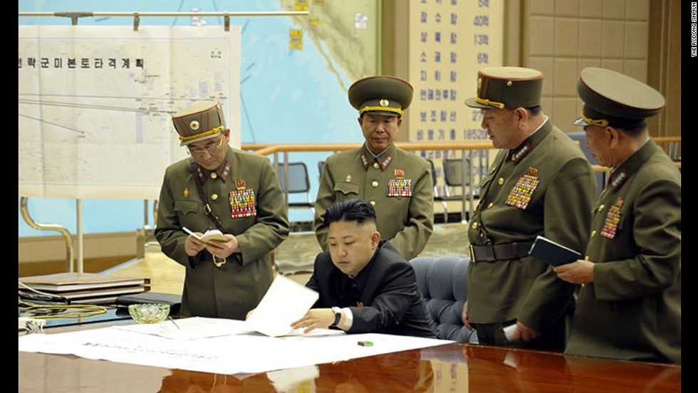 "Kim is briefed by his generals in this undated photo. On the wall is a map titled ""Plan for the strategic forces to target mainland U.S."""