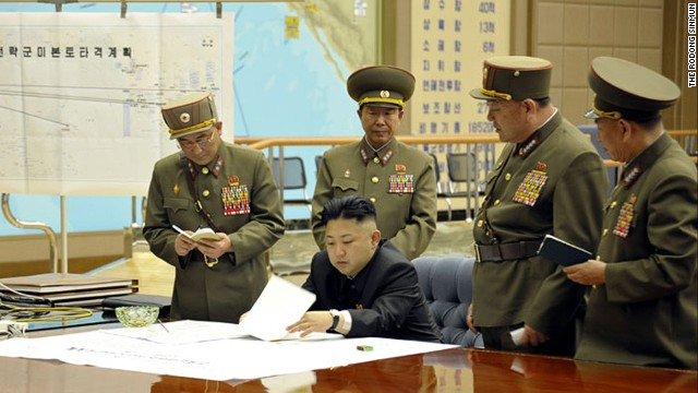 Kim Jong Un being briefed by his generals  (Photo: On the left side of the photo there is a white paper with lines which appears to be a map. The title in Korean of the map goes ìPlan for the strategic forces to target mainland U.S.î If you view it carefully, there is a line leading to what appears to be Hawaii, California, and mainland U.S.) )