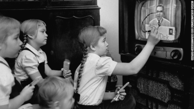 "A girls uses her ""Winky Dink"" drawing kit to draw on a TV screen as they watch the 1950s kids program."