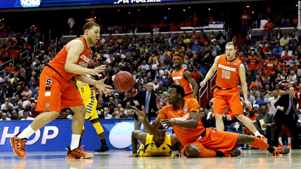 Jerami Grant of Syracuse, bottom right, passes the ball to Brandon Triche, left, from the ground on March 30.