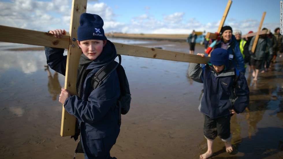 Pilgrims walk with crosses on the final leg of the Northern Cross pilgrimage to Holy Island in Berwick-upon-Tweed, England, on Friday, March 29. More than 50 people, young and old, celebrated Easter by crossing the tidal causeway during the annual Christian pilgrimage.