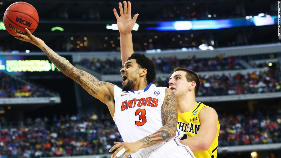 Mike Rosario of Florida shoots past Mitch McGary of Michigan.