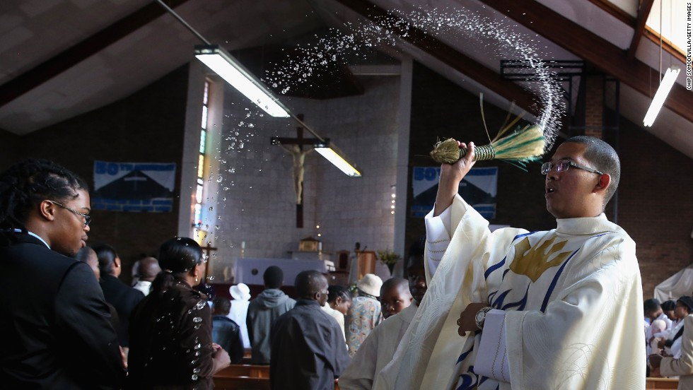 The Rev. Sebastian Rossouw O.M.I. sprinkes holy water on congregants during Easter services at Regina Mundi Catholic Church in the Soweto area of  Johannesburg, South Africa, on Sunday, March 31.