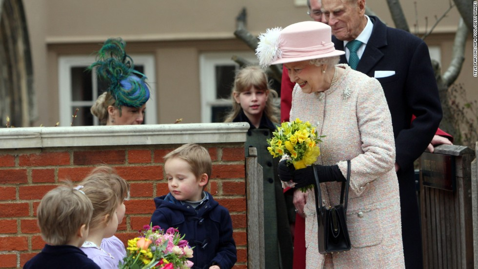 Queen Elizabeth II receives flowers from local children as she leaves the Easter Day service at St. George's Chapel in the grounds of Windsor Castle on March 31.