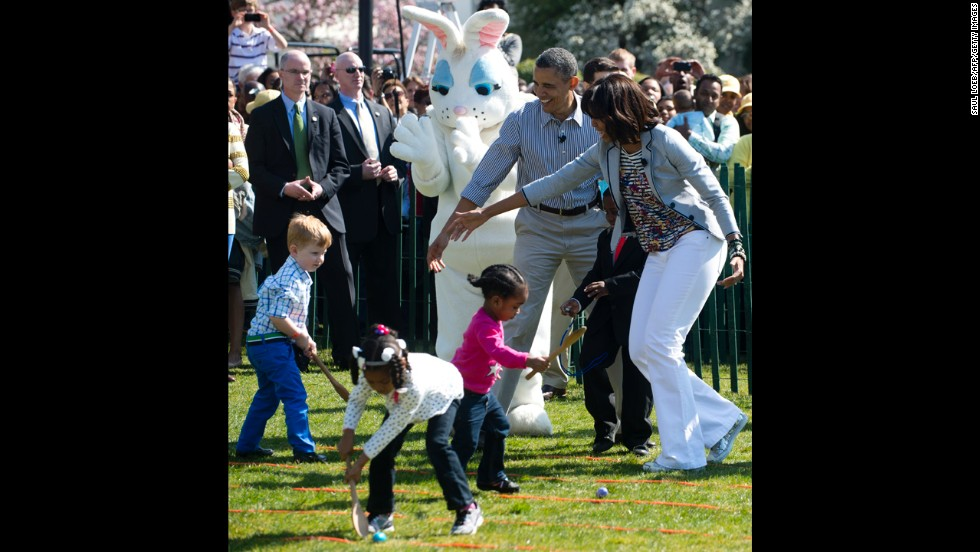 Barack and Michelle Obama cheer on children participating in the egg roll race.