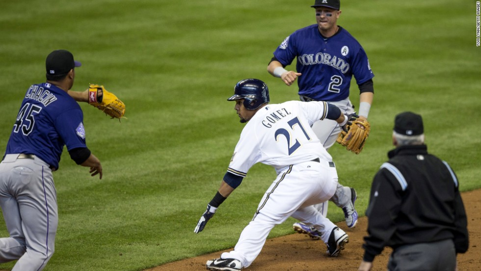 Carlos Gomez of the Milwaukee Brewers is tagged out during a rundown by Jhoulys Chacin of the Colorado Rockies, left, in the first inning.