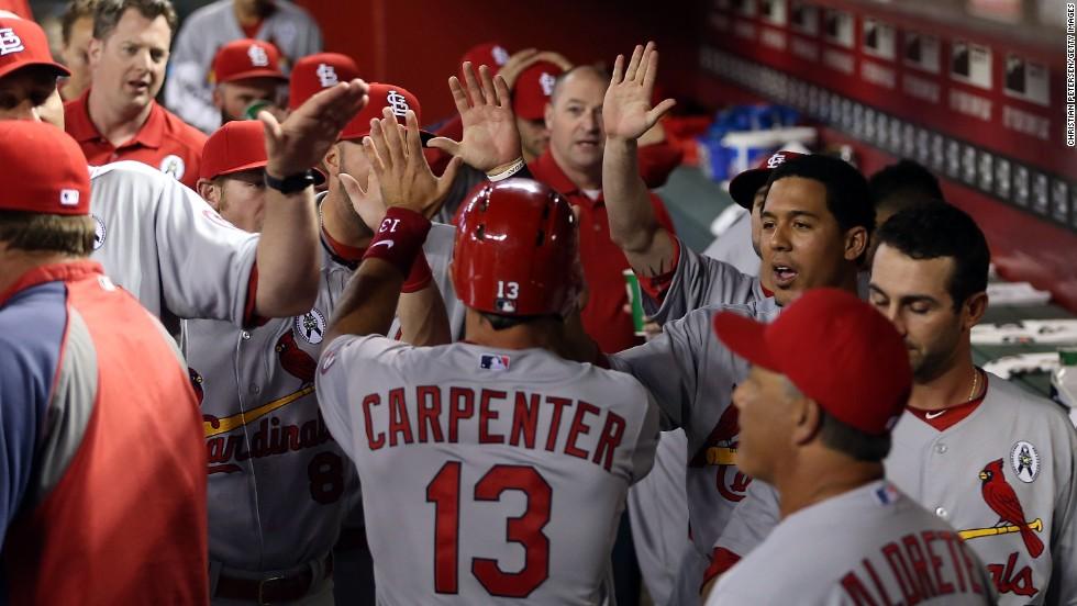 Cardinal teammates congratulate Matt Carpenter in the dugout after he scored a first-inning run.