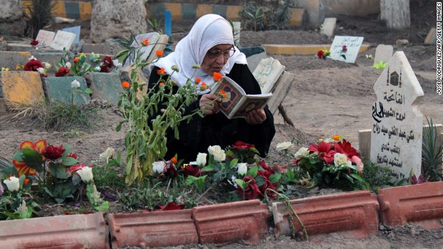 TO GO WITH AFP STORY BY JOSE RODRIGUEZ- A woman reads the Koran, the Muslim holy book, next to the grave of one relative buried in a public park on March 11, 2013 in Syria's eastern city of Deir Ezzor. Men, women and children, and sometimes fighters barely out of adolescence -- every day Al-Mashtal park in the city becomes the final resting place for new victims of the conflict that has torn Syria apart for over two years. AFP PHOTO / JOSE RODRIGUEZ (Photo credit should read JOSE RODRIGUEZ/AFP/Getty Images)