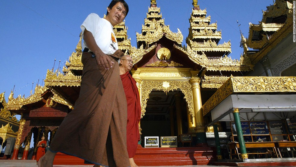 The traditional Burmese dress is the longyi, a wraparound skirt worn by men and women. Men tie theirs in the front and women fold the cloth over and secure it at the side. Here, a longyi-clad visitor walks inside the Shwedagon Pagoda in Yangon.