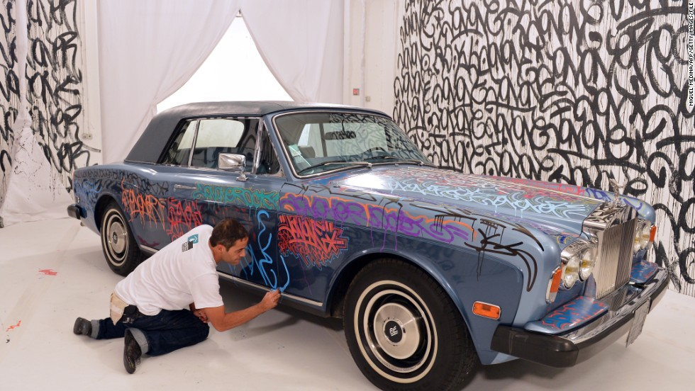 U.S. graffiti artist Jonone performs a painting on a Rolls Royce car owned by former Manchester United and France football player turned actor Eric Cantona during a television show.