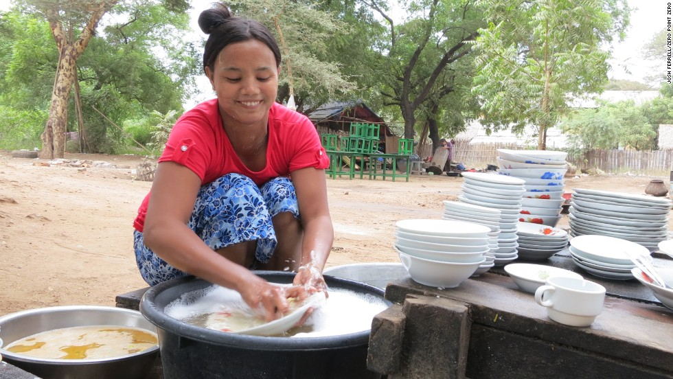 A worker washes dishes in the back of the curry stand, Sarabha, in Old Bagan.