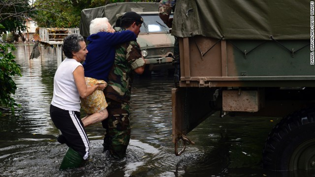 A soldier carries an elderly woman as residents evacuate La Plata on April 3.