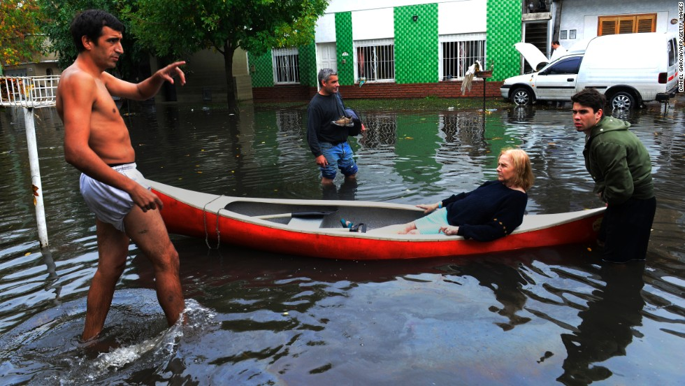 Neighbors help a woman with a canoe on April 3 in a flooded street of La Plata.