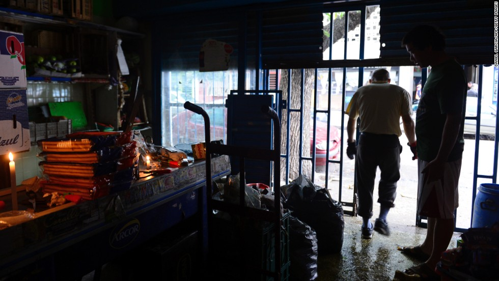 A worker walks out of a supermarket that was flooded and lost power on April 3 in the neighborhood of Belgrano in Buenos Aires.