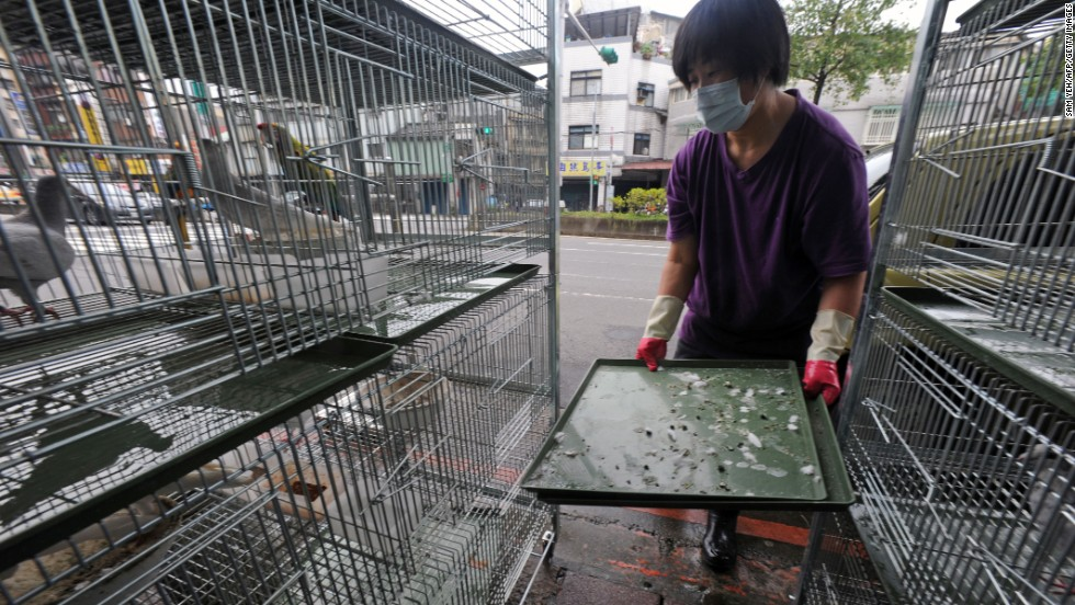A woman cleans a birdcage at a store in Taipei, Taiwan, on Thursday, April 4.