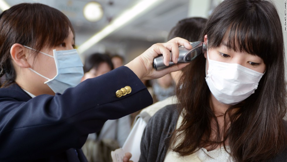 A passenger has her temperature checked by a CDC staff member at the entrance of Sungshan Airport in Taipei.
