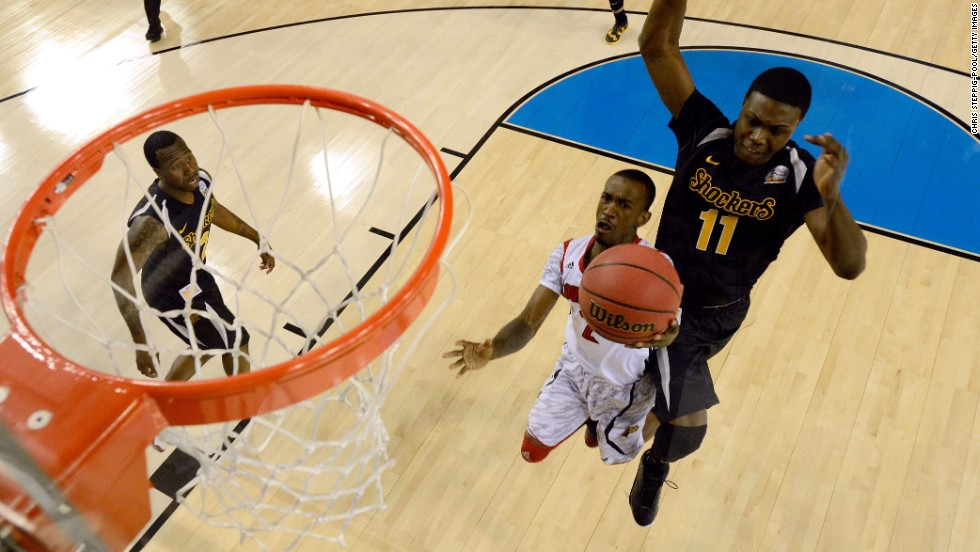 Russ Smith of Louisville drives for a shot attempt in the first half against Cleanthony Early of Wichita State, right.