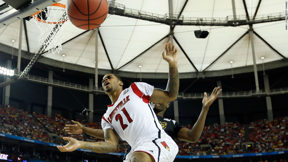 Chane Behanan of Louisville and an unidentified Wichita State player go after a loose ball under the basket.