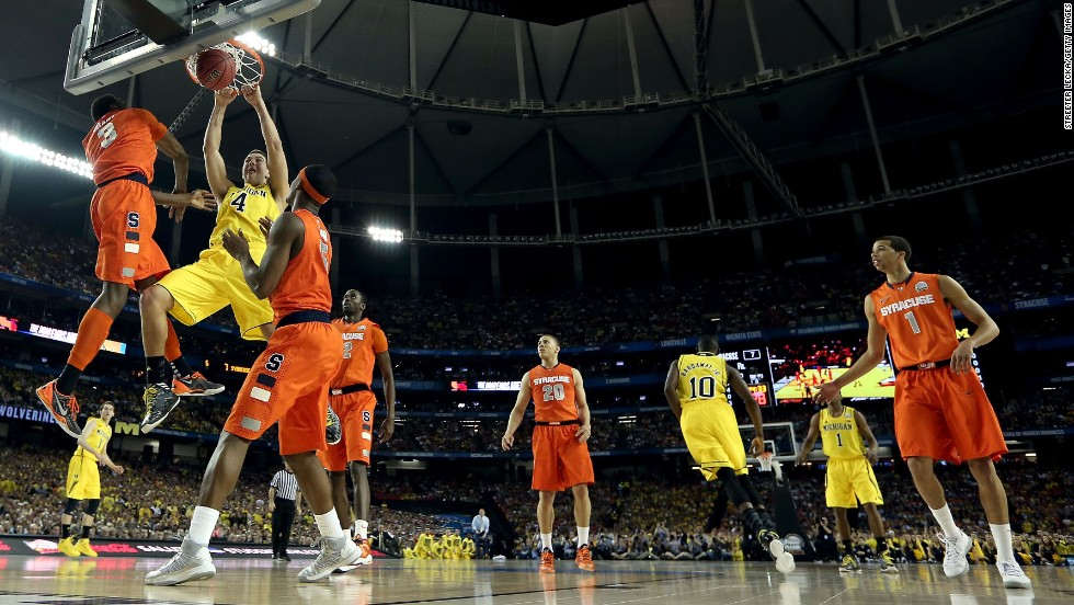 Mitch McGary of Michigan dunks over Syracuse defenders.