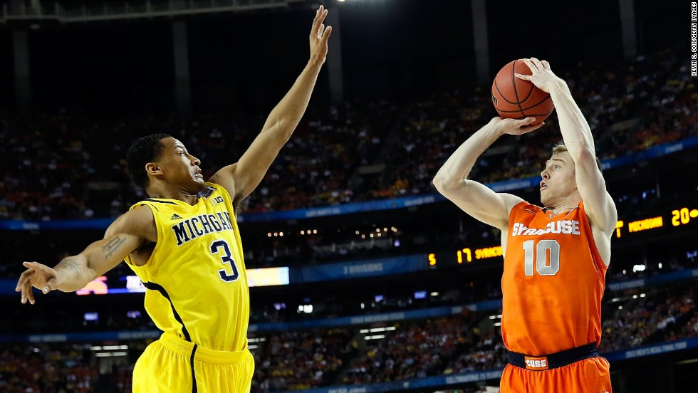 Trevor Cooney of Syracuse shoots a three-pointer over Trey Burke of Michigan.