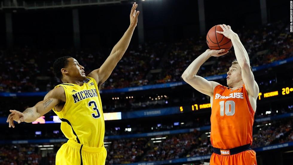 Trevor Cooney of Syracuse shoots a three-pointer over Trey Burke of Michigan.