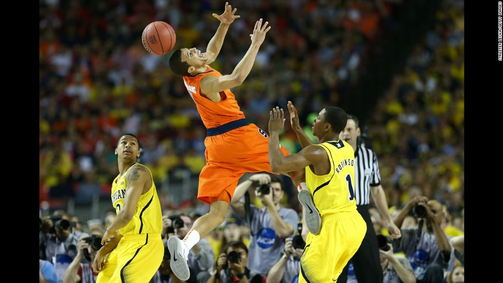 Michael Carter-Williams of Syracuse loses the ball against Glenn Robinson III, right, of Michigan.