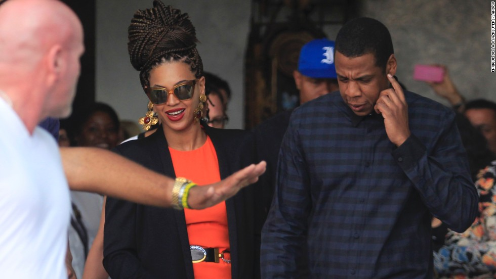 Beyonce and Jay-Z are escorted by bodyguards as they leave their hotel in Havana on Thursday, April 4.