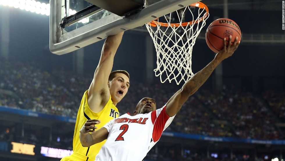Russ Smith of Louisville drives for a shot against Mitch McGary of Michigan.