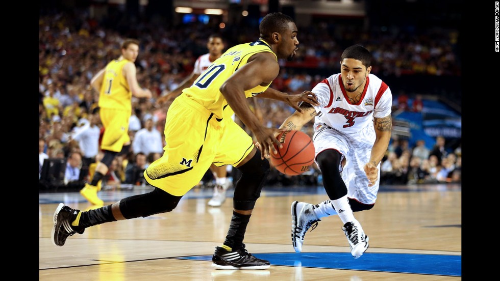 Peyton Siva of Louisville attempts to steal the ball from Tim Hardaway Jr. of Michigan.