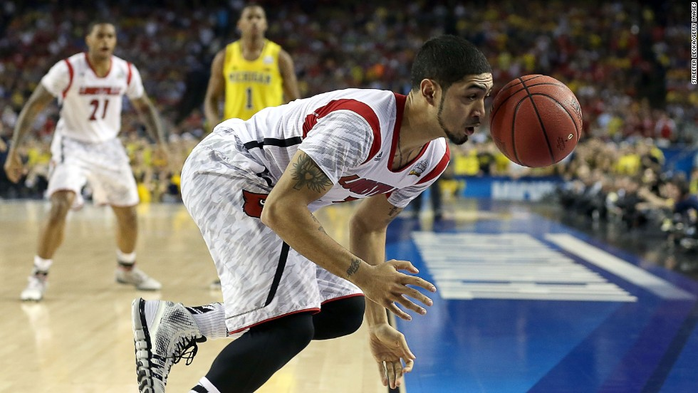 Peyton Siva of the Louisville Cardinals attempts to save the ball from going out of bounds against the Michigan Wolverines.