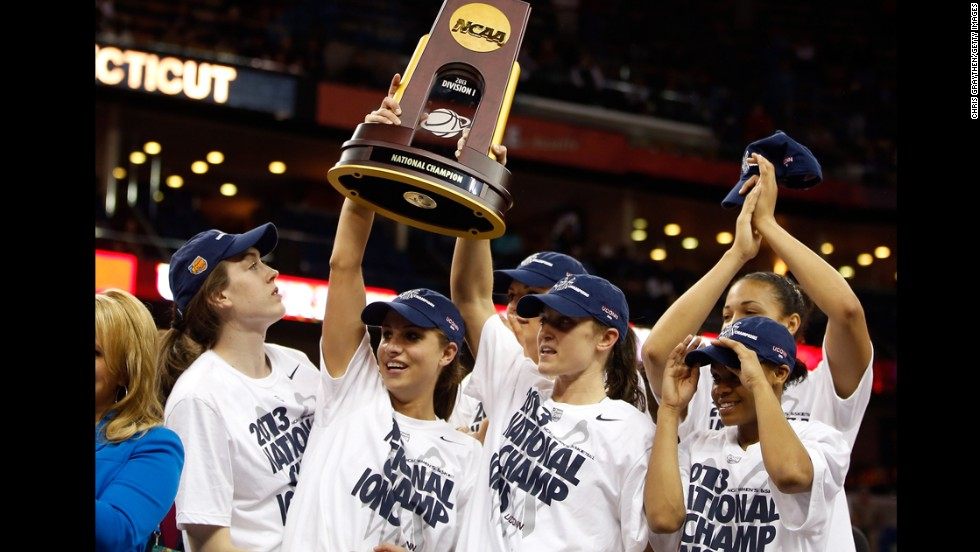 UCONN players hold up the National Championship trophy with their teammates after defeating the Louisville Cardinals on April 9.