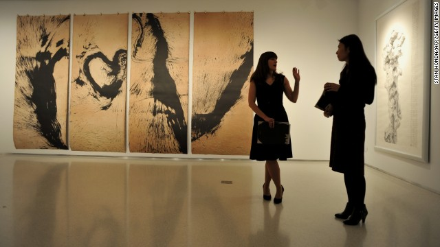 Christie's employees stand in front of a Chinese contemporary ink painting exhibition on February 27 in New York.