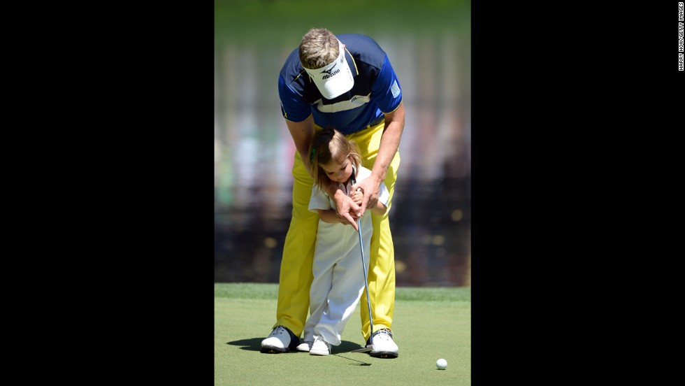 Luke Donald of England putts with his daughter Elle.