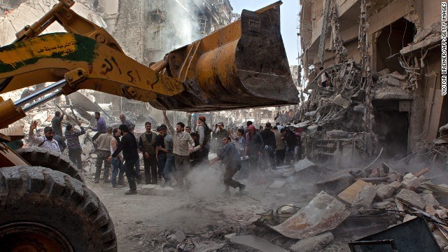 Syrians try to remove large pieces of concrete with the help of a tractor to free those trapped under the rubble following an air strike by government forces on April 7, 2013 that destroyed two five-storey apartment blocks and severely damaged ten buildings in a residential neighbourhood of the northern Syrian city of Aleppo, according to eyewitnesses.