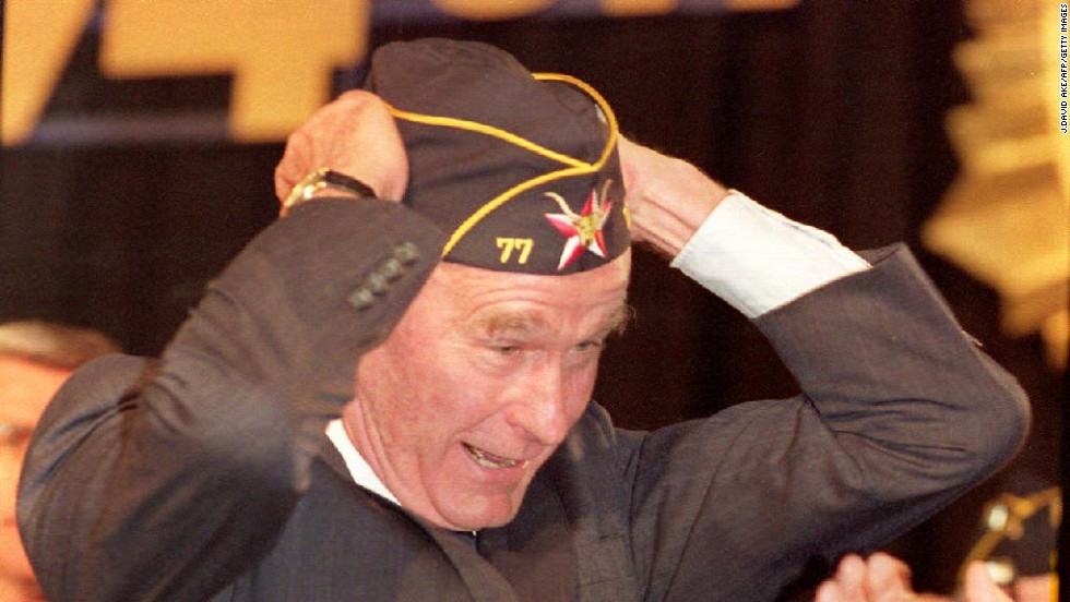 President George Bush tries on a hat given to him by the 74th American Legion at a convention in 1992.