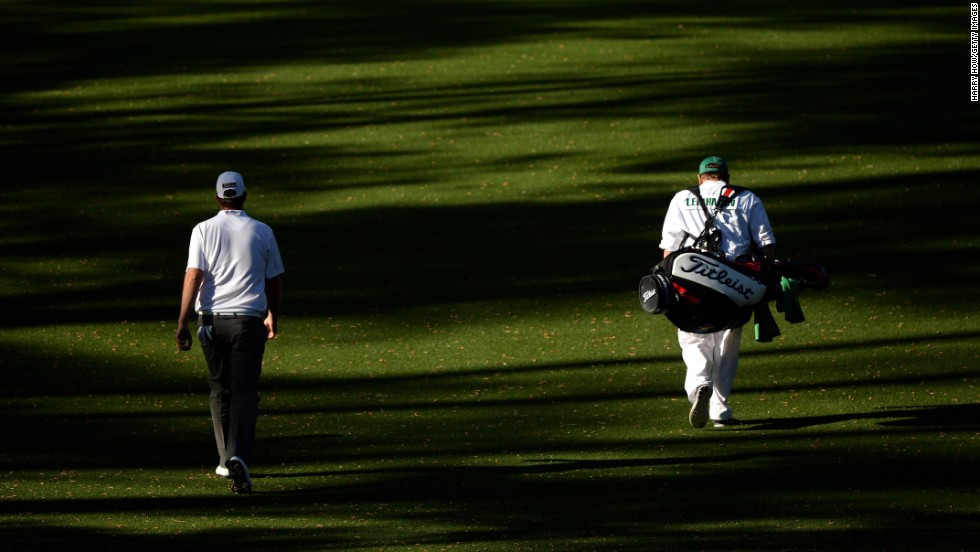 Marc Leishman of Australia walks up the 18th fairway with his caddie Matthew Kelly.
