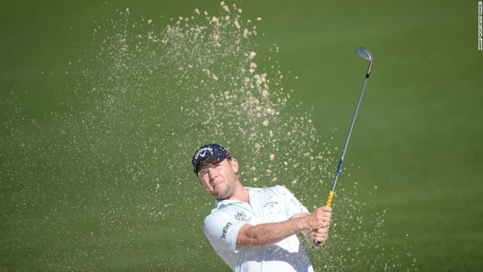 Branden Grace of South Africa hits out of the bunker for eagle on the second hole.