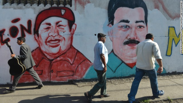 People walk past murals with Hugo Chavez's and Maduro's likeness in Caracas.