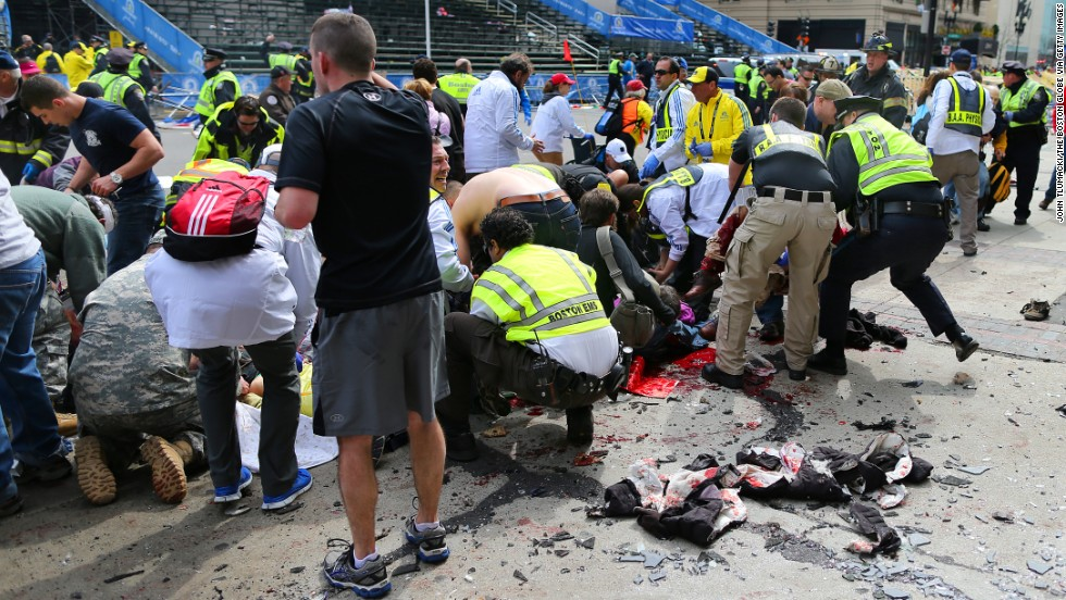 Victims are helped at the scene of the first explosion.