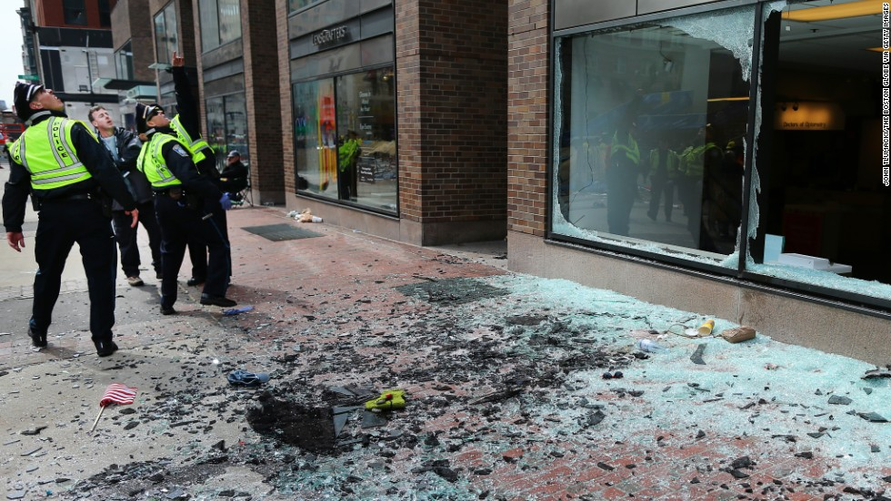 Boston police examine the scene where the first explosion blew out windows on Boylston Street.