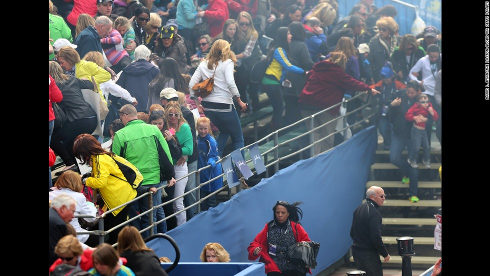 Spectators leave the bleachers after the explosions.